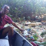 Ademar, morador do Itaguá, no barco fazendo a limpeza do rio