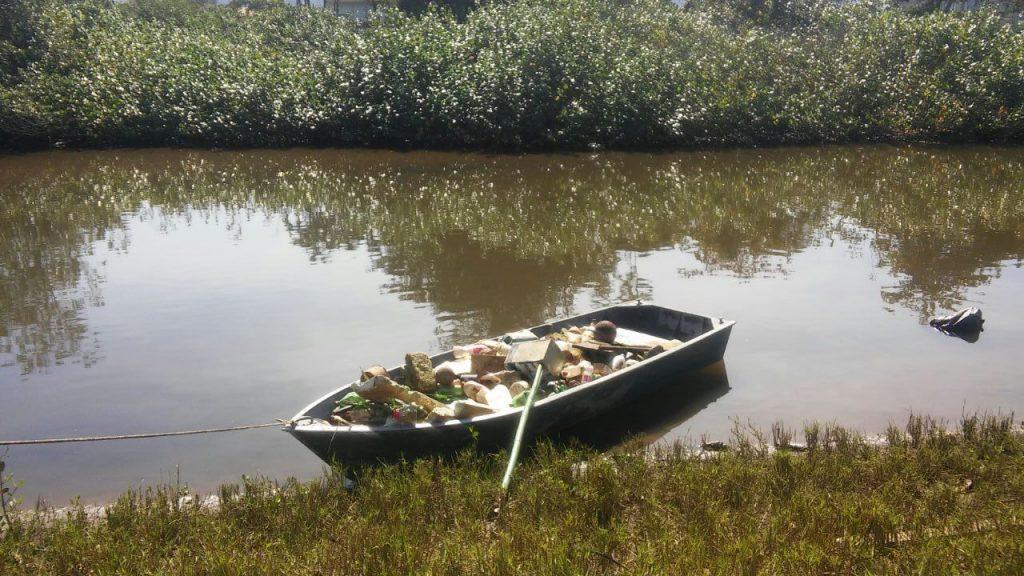 Barco usado na limpeza do rio Tavares com lixo dentro