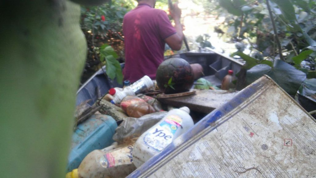Moradores ao lado do lixo no barco usado na limpeza do rio Tavares