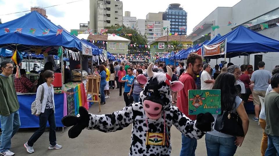 Pessoa vestida de vaca na festa junina vegana do Vegnice